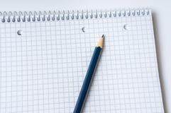 在白色和笔记本隔绝的铅笔 库存图片