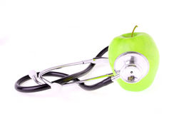 在白色和绿色苹果查出的听诊器 免版税库存图片