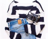 在白色和蓝色条纹、牛仔裤和照相机的毛线衣 免版税库存照片