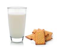 在白色和薄脆饼干隔绝的杯牛奶 图库摄影