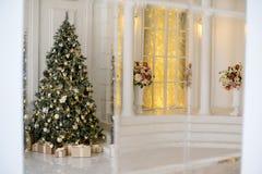 在白色和金黄颜色装饰的时髦的圣诞节内部 图库摄影