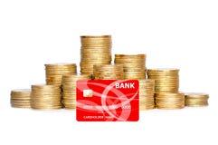 在白色和银行信用卡的许多硬币隔绝的专栏 免版税库存图片