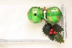 在白色和银餐巾的两个绿色圣诞节球 免版税图库摄影