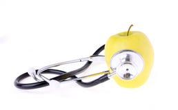 在白色和黄色苹果查出的听诊器 图库摄影