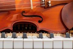 在白色和黑钢琴的古典小提琴锁上特写镜头背景 库存照片
