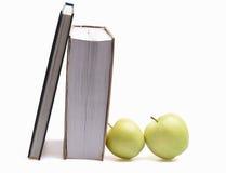 在白色和绿色苹果隔绝的书 库存图片