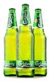 在白色嘉士伯啤酒隔绝的三个瓶 免版税库存图片