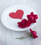 在白色圆的板材的纸心脏和猩红色玫瑰 图库摄影