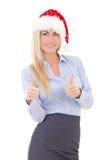 在白色圣诞老人帽子赞许的愉快的女商人隔绝的 免版税库存照片
