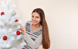 在白色圣诞节树旁边的微笑的少妇 库存图片
