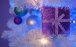 在白色圣诞节树的浅紫色的礼物盒与白光,蓝色光,小野鸭装饰品,紫色装饰品,白色装饰品 免版税图库摄影