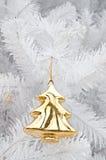 在白色圣诞节结构树的金黄杉木雕象 免版税库存照片