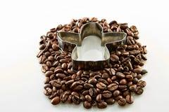 在白色在天使形状附近的咖啡豆隔绝的 库存图片