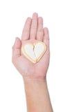 在白色在手中隔绝的残破的华伦泰曲奇饼心脏 免版税库存图片