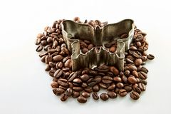 在白色在蝴蝶形状附近的咖啡豆隔绝的 库存照片