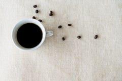 在白色地毯的咖啡豆杯子 免版税库存图片