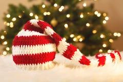 在白色地毯的镶边圣诞老人帽子 图库摄影