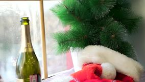 在白色基石的圣诞老人项目帽子反对窗口和人为云杉的分支 红色帽子,打开了瓶闪耀 股票录像