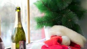 在白色基石的圣诞老人项目帽子反对窗口和人为云杉的分支 红色帽子,打开了瓶闪耀 影视素材