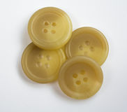 在白色堆积和隔绝的四个米黄色的塑料按钮 免版税图库摄影