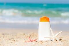 在白色塑料瓶在热带海滩,夏天辅助部件的防护遮光剂或sunblock和sunbath化妆水在假日, 库存图片
