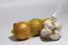 在白色塑料网的白色在浅灰色的背景隔绝的黄色塑料网的大蒜和葱 免版税库存照片