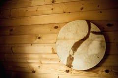 在白色墙壁上垂悬的老木小手鼓 图库摄影