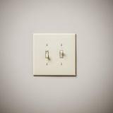 在白色墙壁上的双重Lightswitch 免版税库存照片