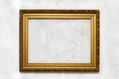 在白色墙壁上的古金色框架 库存照片