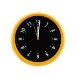 在白色墙壁上的圆的黄色时钟 图库摄影