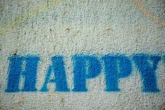 在白色墙壁上的愉快的蓝色油漆词街道画 免版税库存图片