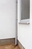 在白色墙壁上的新的金属雨天沟有窗口的 免版税库存图片