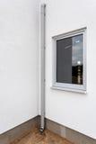 在白色墙壁上的新的雨天沟有窗口的 库存照片