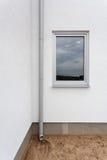 在白色墙壁上的新的雨天沟有窗口的 免版税库存照片