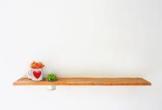 在白色墙壁上的木架子有绿色植物和杯子心脏的 免版税库存照片