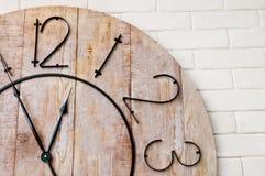在白色墙壁上的木clockface 库存照片