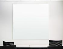 在白色墙壁上的空白的方形的委员会 库存照片