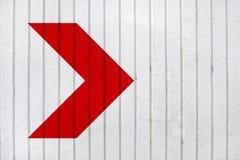 在白色墙壁上的红色箭头 免版税库存照片
