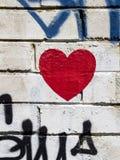 在白色墙壁上的红色街道画心脏 图库摄影