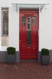 在白色墙壁上的红色门有玻璃的 免版税库存图片