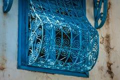 在白色墙壁上的美丽的装饰蓝色窗口很典型为 库存照片