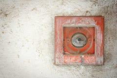 在白色墙壁上的老按钮火警 免版税库存图片
