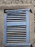 在白色墙壁上的老蓝色木窗口由大气阿格纳损坏了 免版税库存图片