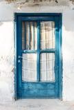 在白色墙壁上的老蓝色木门 免版税库存照片