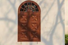在白色墙壁上的老被成拱形的木窗口有树麸皮的阴影的 免版税库存照片