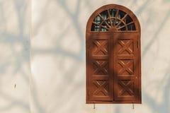 在白色墙壁上的老被成拱形的木窗口有树麸皮的阴影的 免版税库存图片