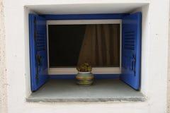 在白色墙壁上的葡萄酒蓝色窗口 希腊 库存图片