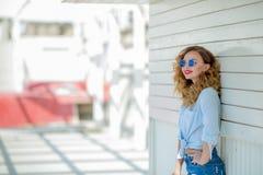 在白色墙壁上的陡峭的惊人的女孩,棕榈 穿戴在牛仔布短裤,衬衣,军事样式,伪装,辅助部件 免版税库存图片