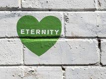 在白色墙壁上的绿色街道画心脏 免版税图库摄影
