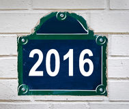 在白色墙壁上的巴黎街道板材写的2016年 库存照片